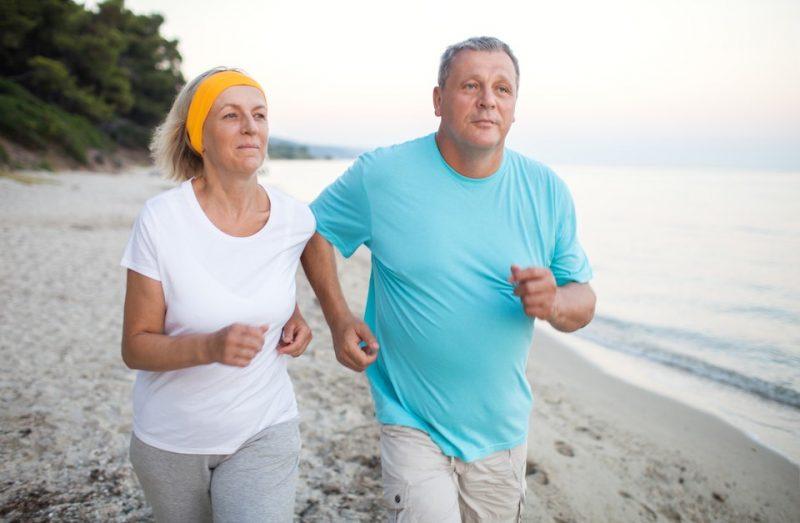 courir sur la plage par une femme et un homme senior